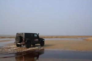 Jeep Wrangler fahrt am Strand
